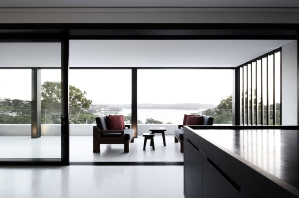 Interior opening on a balcony with a glazed balustrade that divides it from the deep vista over the sea.