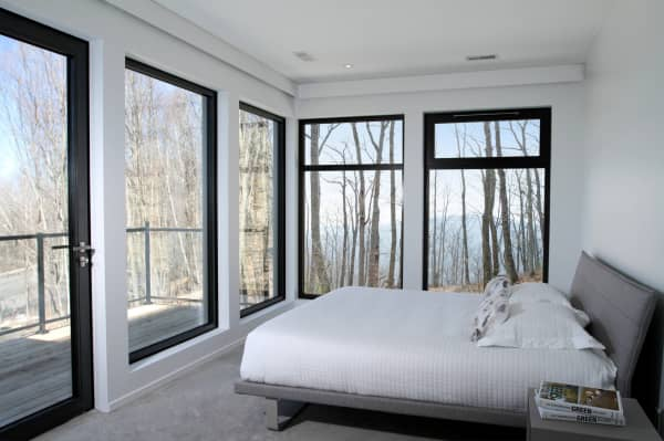 Small bedroom with large windows that make the room look bigger.