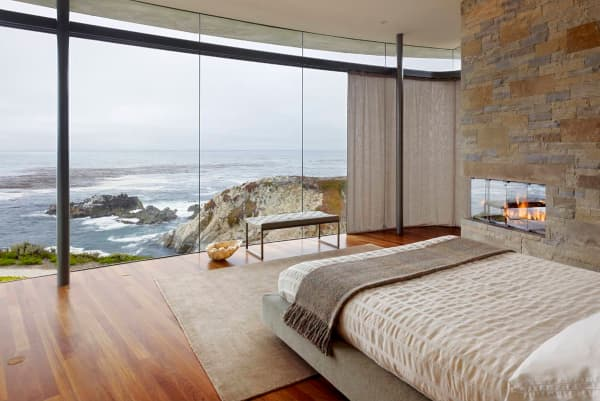Bedroom with fully glazed wall looking into the sea.