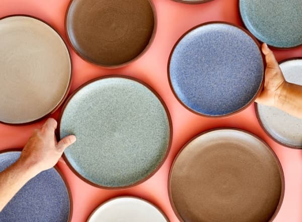 Flatlay shot of several Granbyware plates on an orange background.