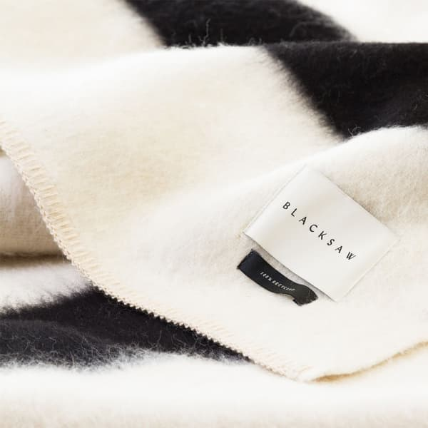 """Close-up view of the blanket, clearly showing the """"100% recycled"""" tag."""