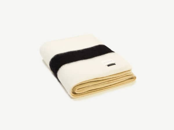 White blanket with a black stripe on the bottom.