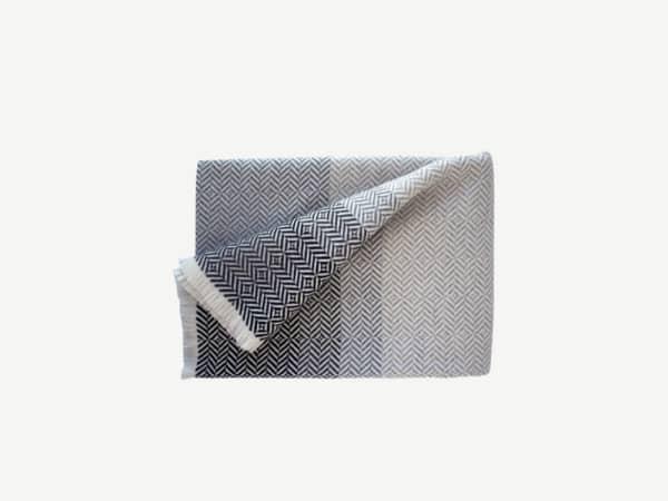 Grey blanket with a herringbone white pattern.