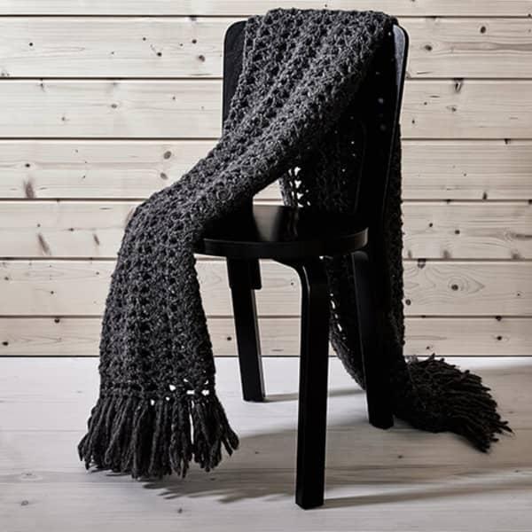 Dark grey crocheted blanket lying on a chair.