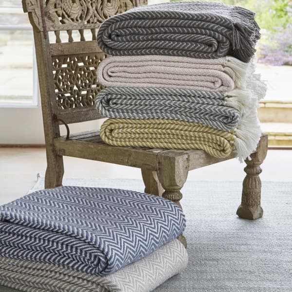 A pile of blanket stacked onto a Moroccan style low chair.