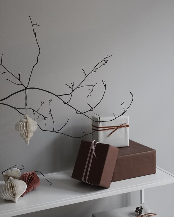 Branch decorated with paper ornaments in earthy tones.
