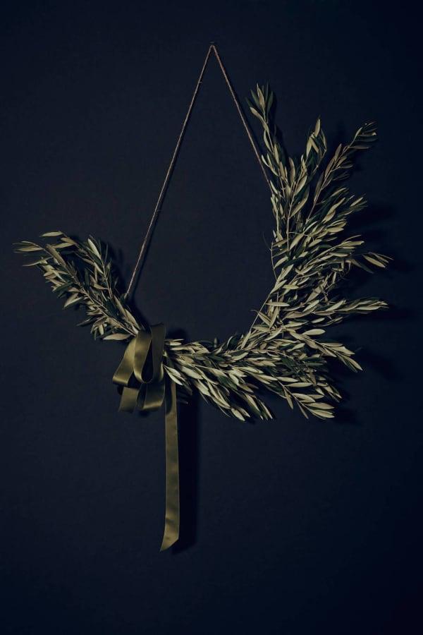Olive twigs asymmetric wreath on a dark blue background.