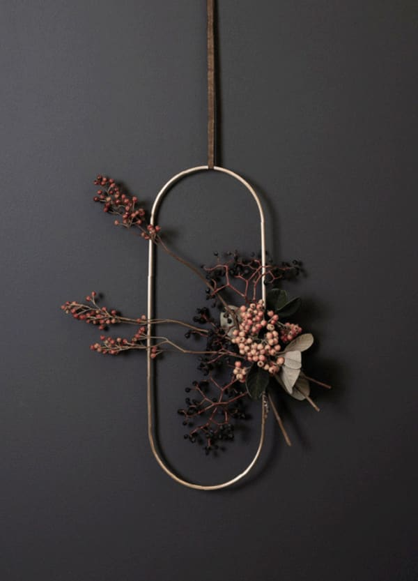 Oval metal wreath decorated with berry branches.