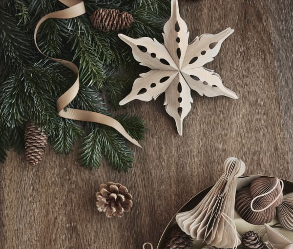 Paper sustainable Christmas ornaments on a wood background.