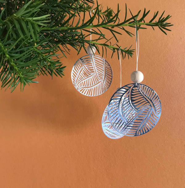 Paper cut ornament made with a silver foiled paper.