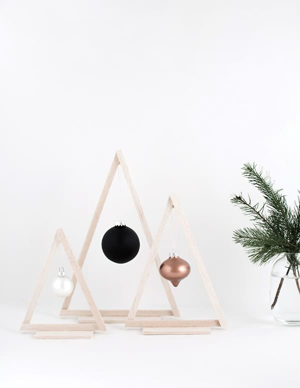 Wood triangles with a bauble hanging in the middle are a minimal interpretation of a Christmas tree.