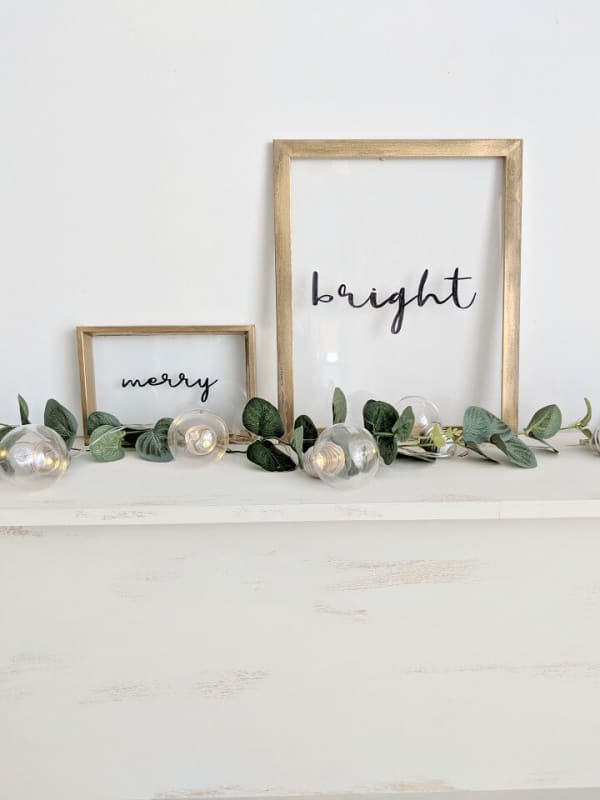 """""""Merry"""" and """"Bright"""" words written into the glass on a picture frame."""