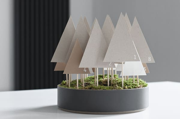 Advent calendar made of paper trees mounted on a wooden stick and tucked in a container onto a moss base.
