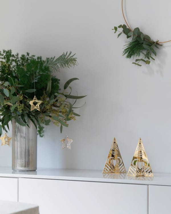 Festive vignette created with real greenery and golden metal ornaments.