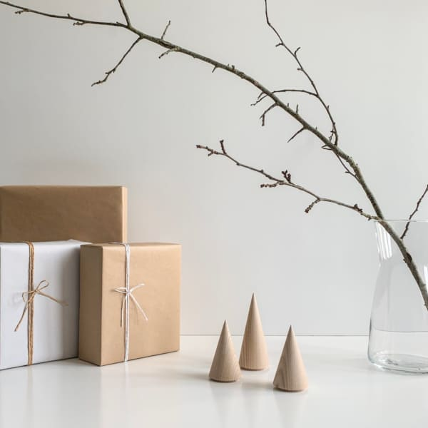 Wooden minimal trees on a table with gifts next to them.