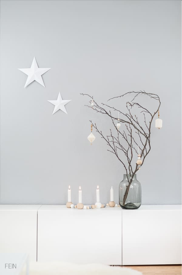 Branch decorated with white ornaments on a light grey wall background.