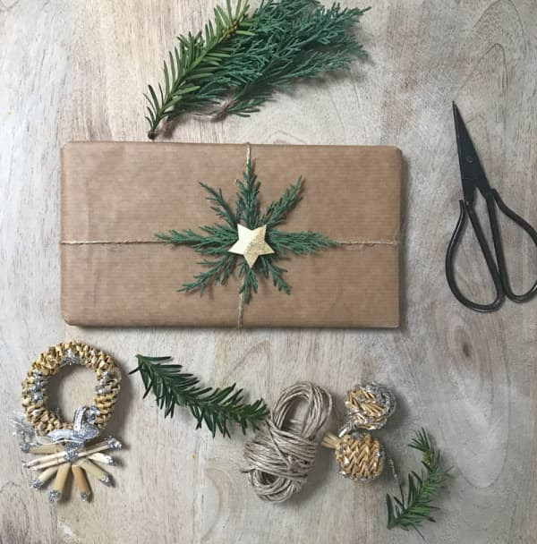An example of sustainable Christmas gift wrapping where simple brown paper is decorated with some greenery twigs arranged radially and a golden star in the center.