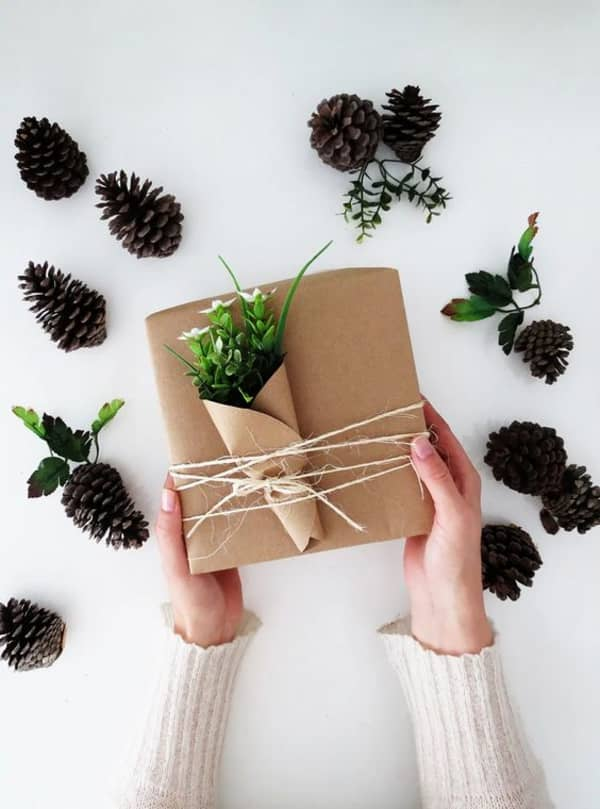 Gift wrapped in brown paper and decorated with few twigs wrapped into brown paper like a flower bundle.