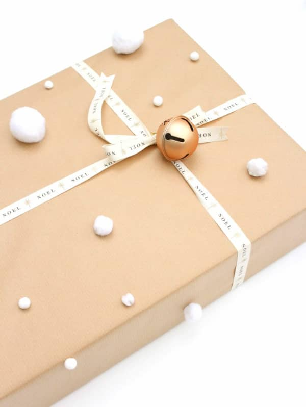 Brown paper gift wrapping decorated with a small bell and white fabric pompoms all around.