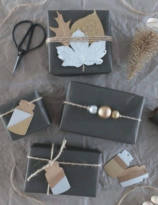 Black wrapping paper decorated with leaves, wood ornaments and cardboard cutouts.