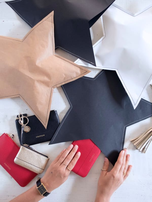White, black and brown paper cut in the shape of a star a stitched to make a creative gift wrapping.