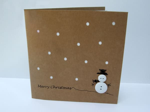 Christmas card with two white buttons representing the body of a snowman and the hat drawn with black pen.
