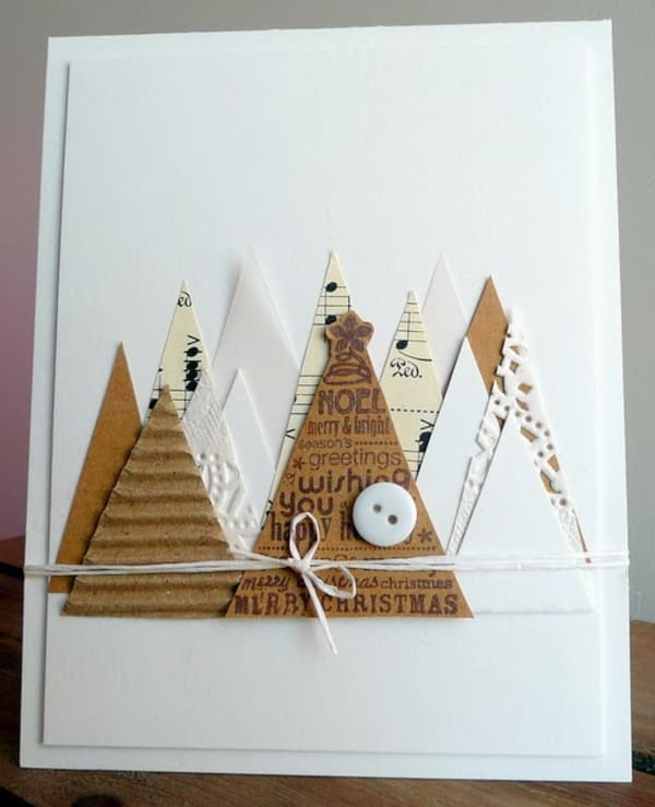 White Christmas card decorated with triangular cut-outs representing Christmas trees.