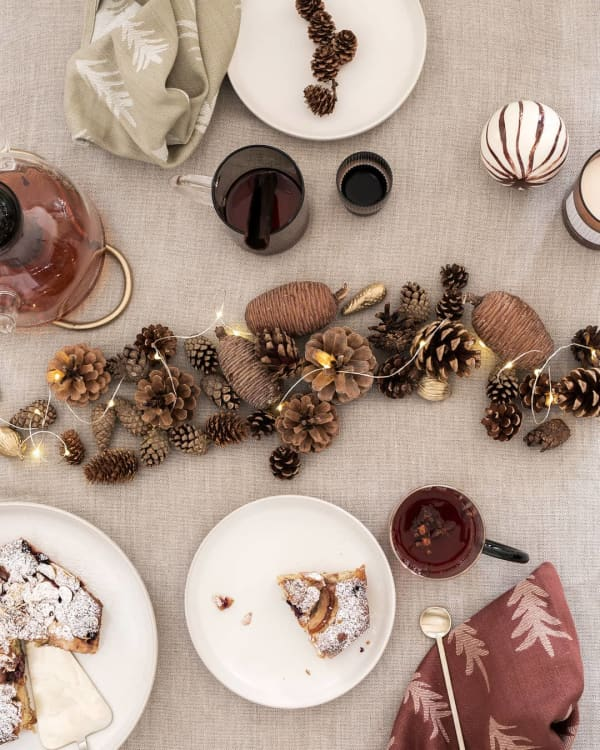 Top shot of a festive table setting with pinecones and string lights creating a sustainable Christmas centrepiece in the middle of the table.