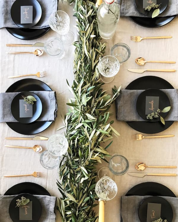 Black and gold table setting with olive branches as a centrepiece.