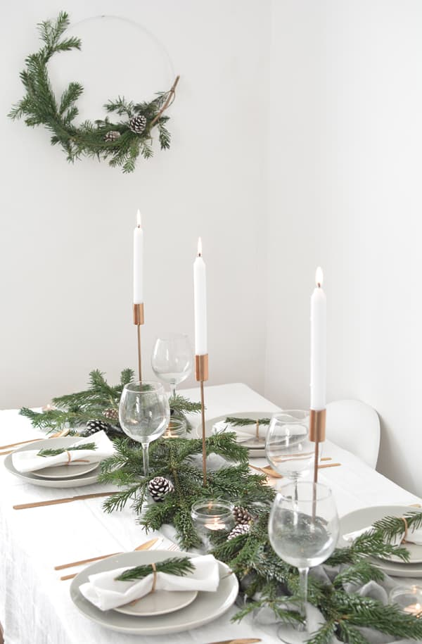 Total white festive table setting with greens and tall candles as a centrepiece.