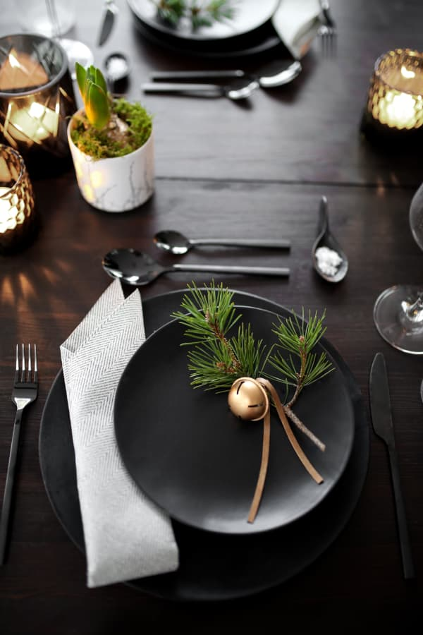 Two twigs and a golden bell over a black plate.