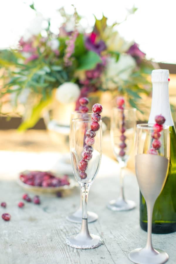 A stick made of frozen cranberries adds a festive vibes when put into a champagne glass.