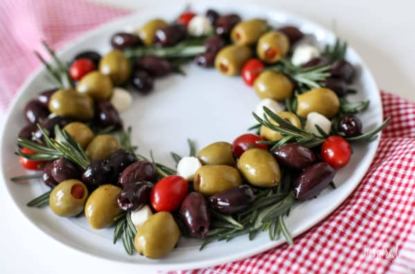 Rosemary and olives arranged in the shape of a wreath on a white plate.