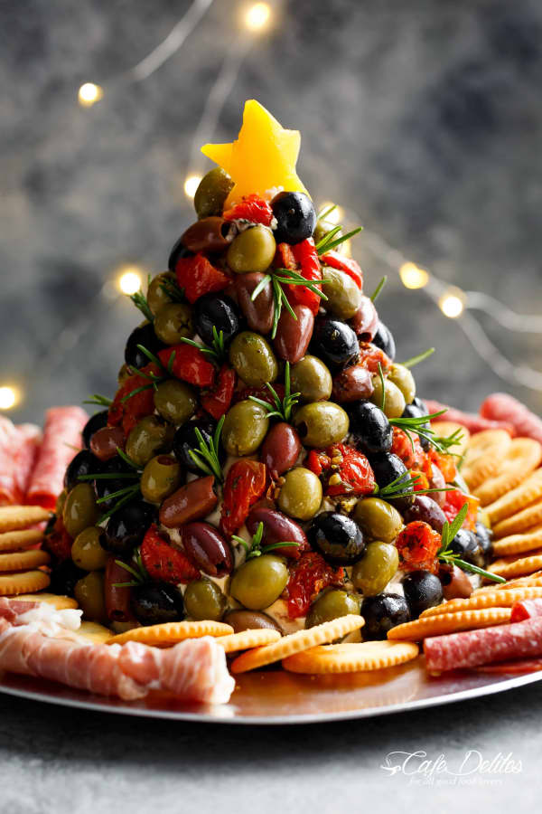 Olives and dried tomatoes arranged in the shape of a Christmas tree.
