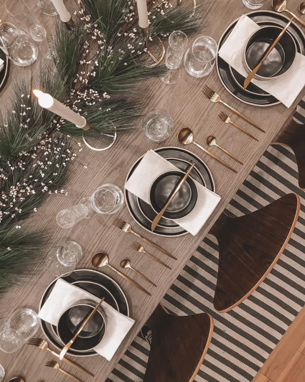 Black and light wood table setting with branches and tall candles as a centrepiece.