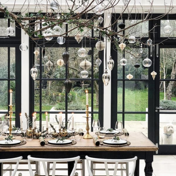 Branch with vintage ornaments hung over a modern dining table.