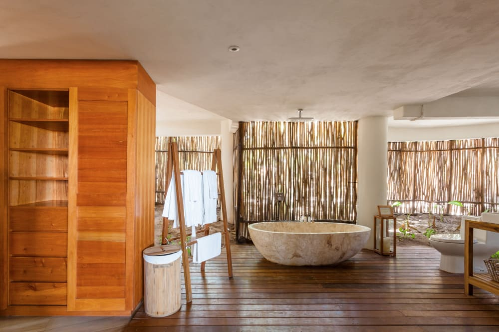 """Bathroom of Casa Nalum: the wall is made of bamboo canes that let plenty of natural light in.<span class=""""sr-only""""> (opened in a new window/tab)</span>"""