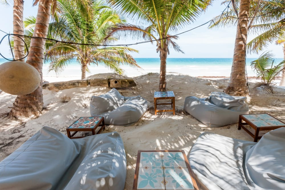 """The outdoor lounging area of Casa Nalum sits directly on the beach.<span class=""""sr-only""""> (opened in a new window/tab)</span>"""