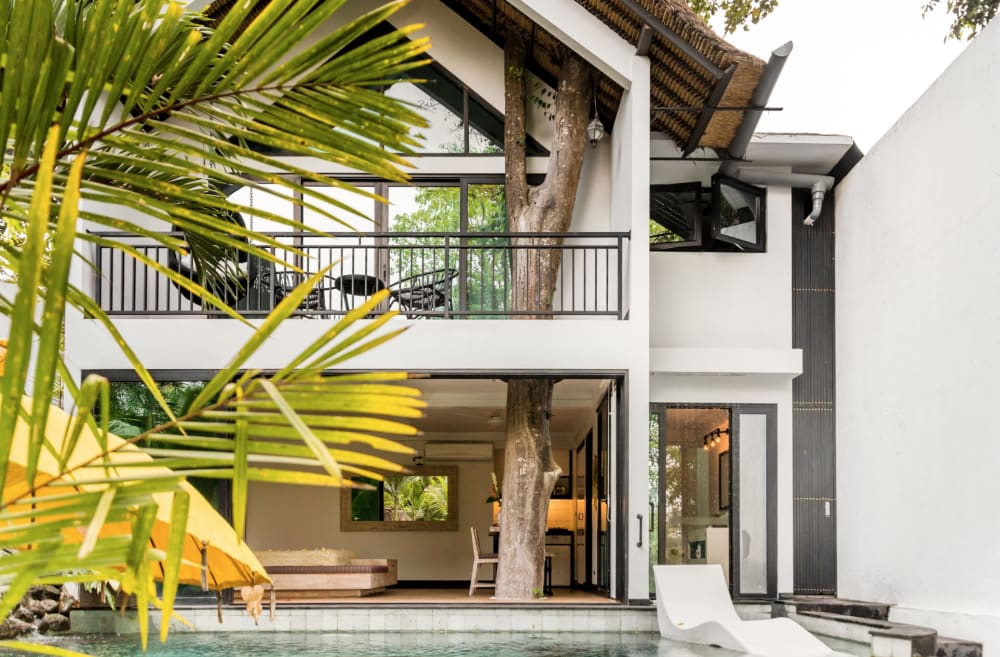 """Outdoor of the house, showing that it's built around a tree.<span class=""""sr-only""""> (opened in a new window/tab)</span>"""