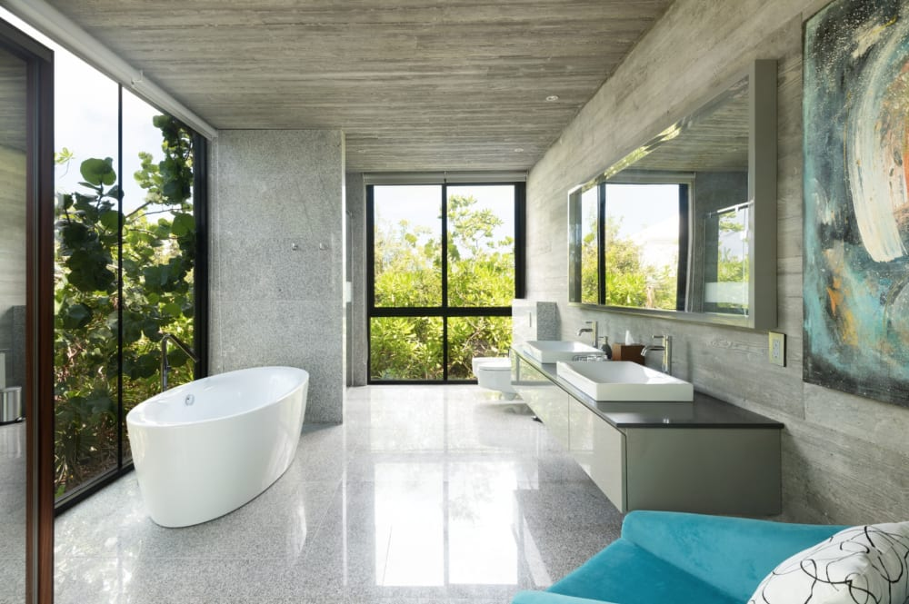 """A bathroom of Villa Islander, with a free-standing bathtub in front of the window that looks directly into nature.<span class=""""sr-only""""> (opened in a new window/tab)</span>"""
