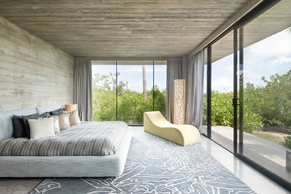 """Bedroom of Villa Islander, with full-height windows that look into the forest.<span class=""""sr-only""""> (opened in a new window/tab)</span>"""