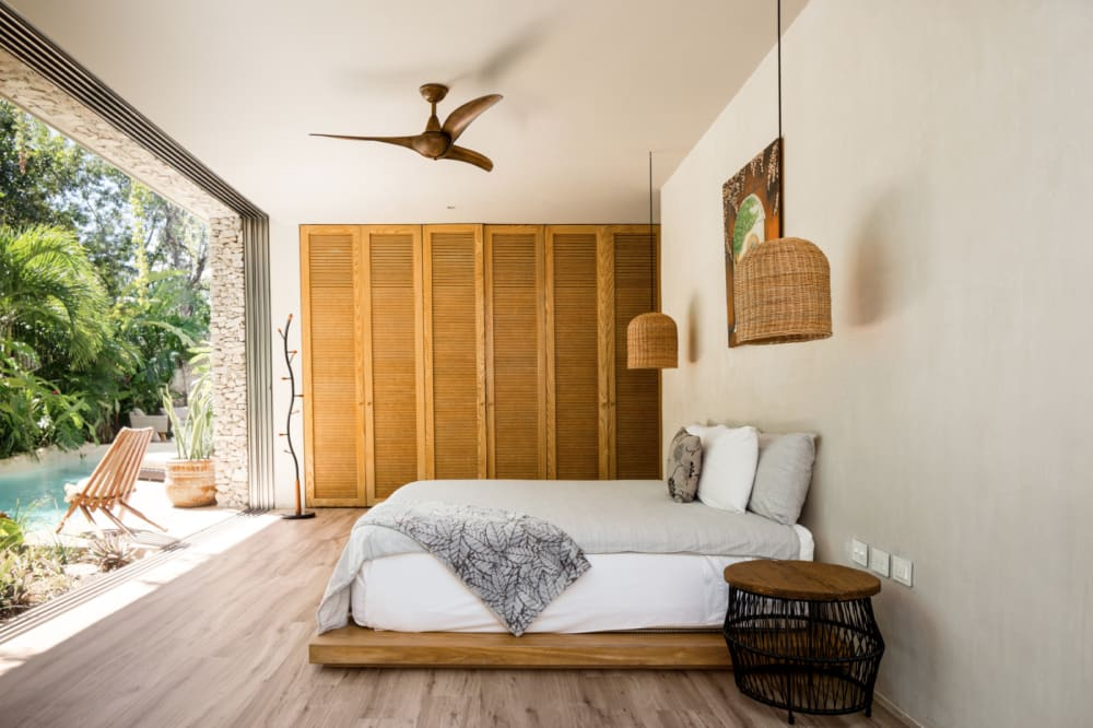 """One of the bedrooms of Villa Verde, with a floor-to-ceiling window in front of the bed.<span class=""""sr-only""""> (opened in a new window/tab)</span>"""