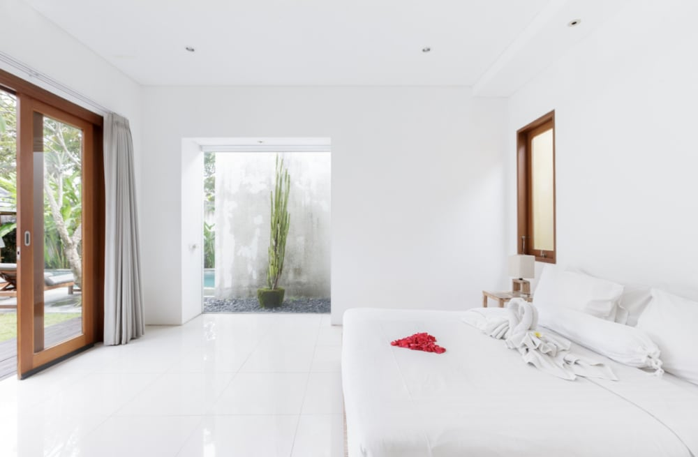 """Bedroom with a glass part of the wall containing plants and opening the view to the outdoors.<span class=""""sr-only""""> (opened in a new window/tab)</span>"""