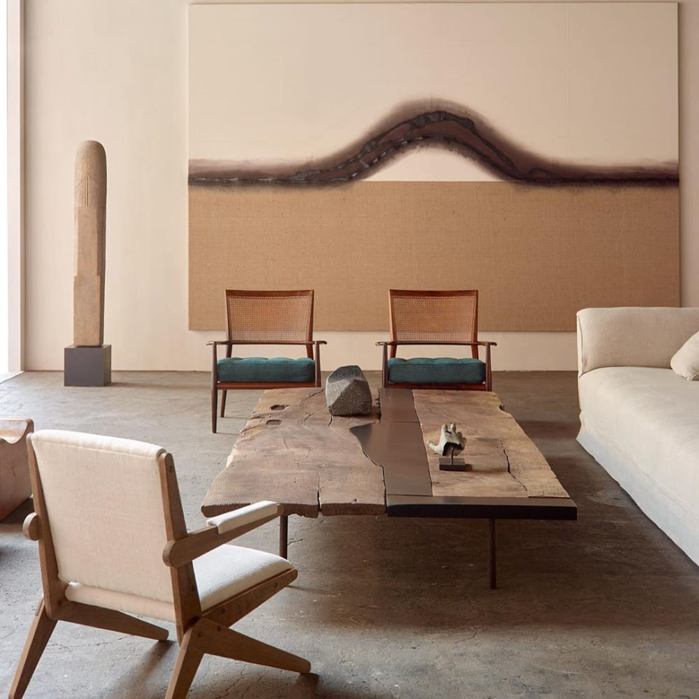 """Sitting area with oversized artwork drawing a bell-shaped curved on the wall.<span class=""""sr-only""""> (opened in a new window/tab)</span>"""