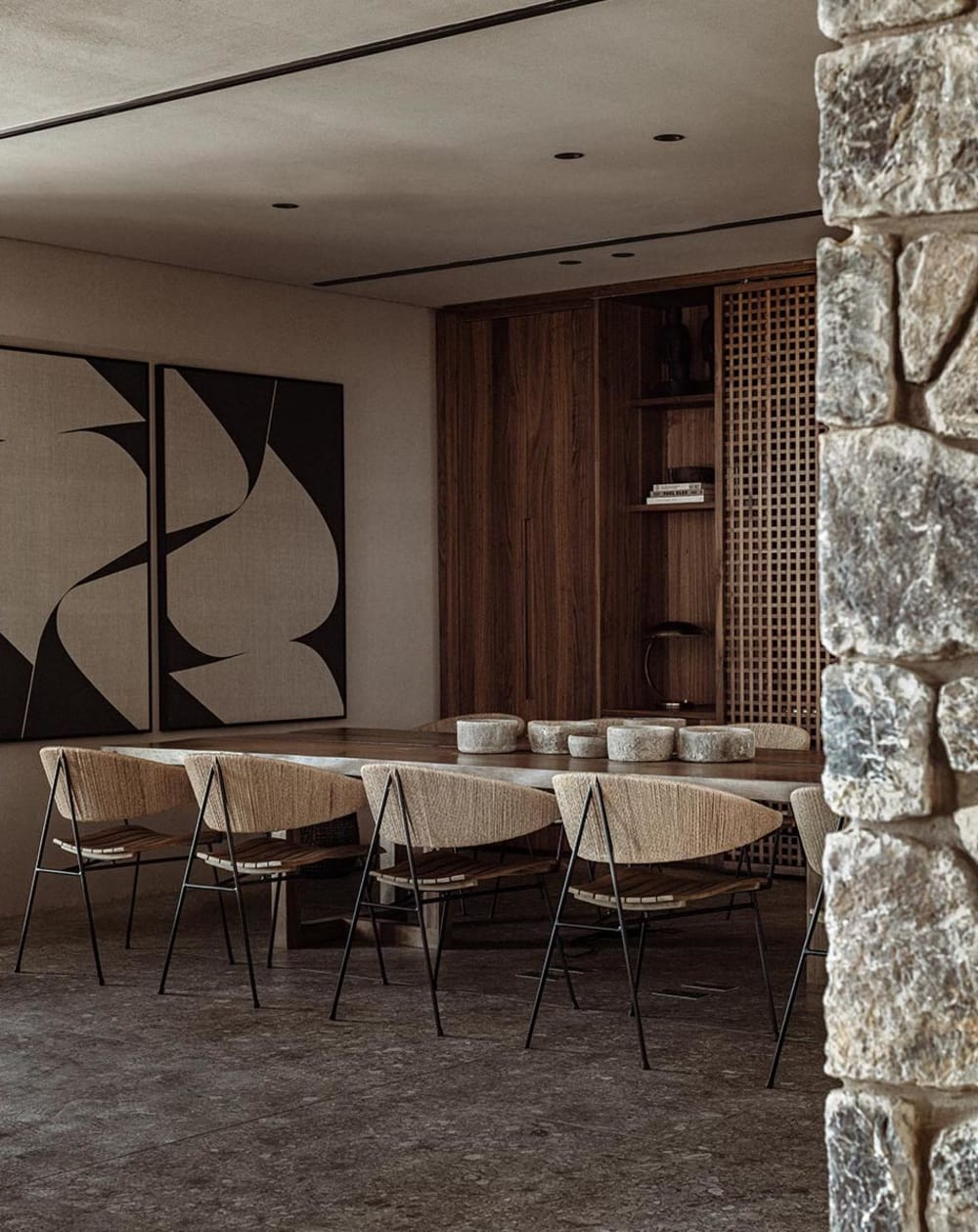 """Biophilic dining room in the tones of Brave Ground. Raw stone wall and chairs with a rope back.<span class=""""sr-only""""> (opened in a new window/tab)</span>"""