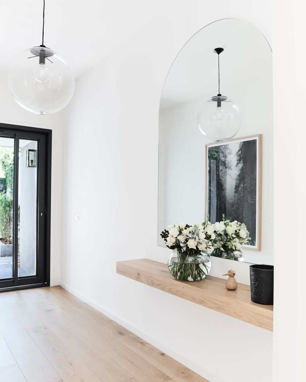 """Contemporary entryway with a wood shelf popping against a white wall.<span class=""""sr-only""""> (opened in a new window/tab)</span>"""