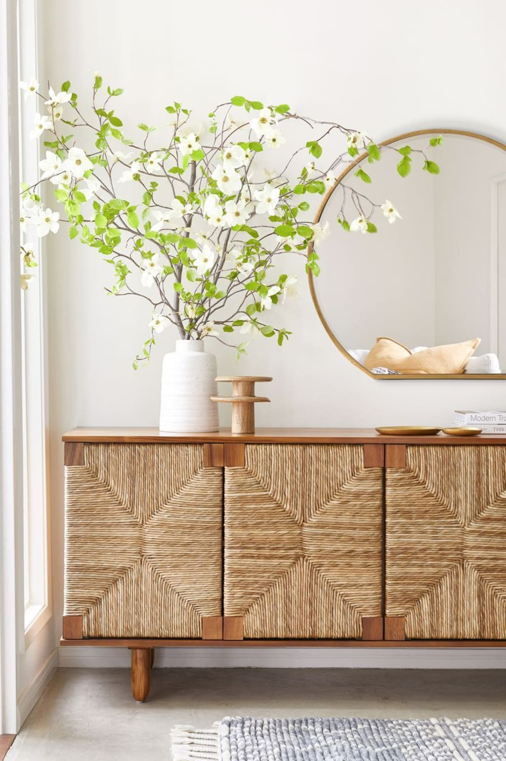 """Entryway with woven console and big flowered branches.<span class=""""sr-only""""> (opened in a new window/tab)</span>"""