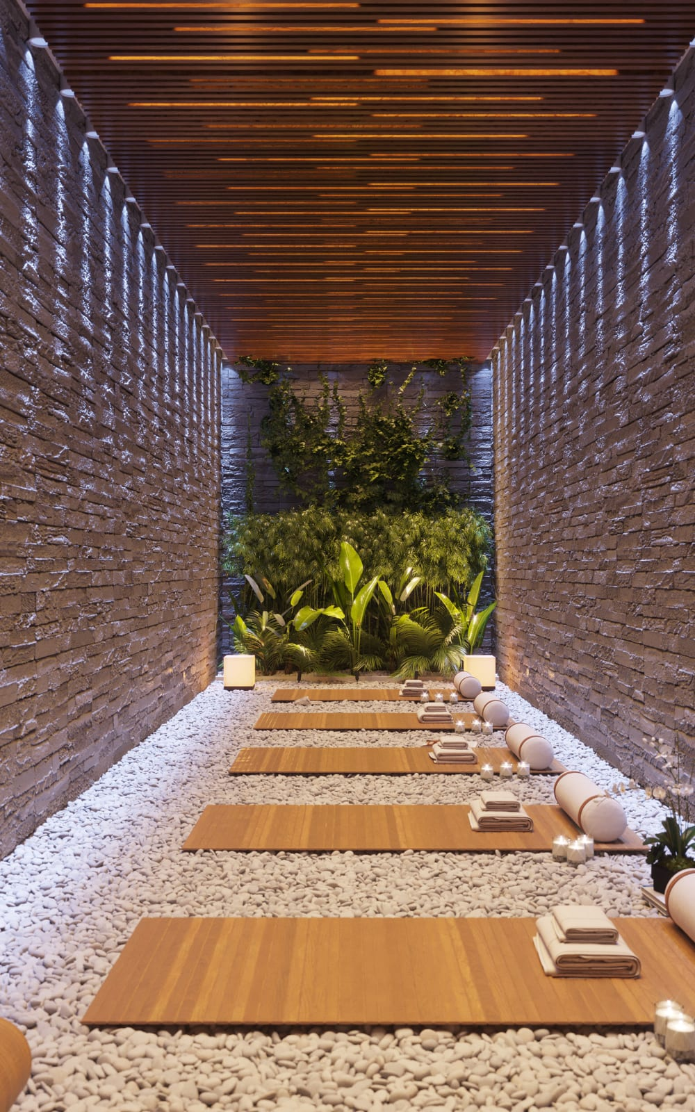 """Meditation room with a green wall feature, stone walls and little pebbles on the ground.<span class=""""sr-only""""> (opened in a new window/tab)</span>"""