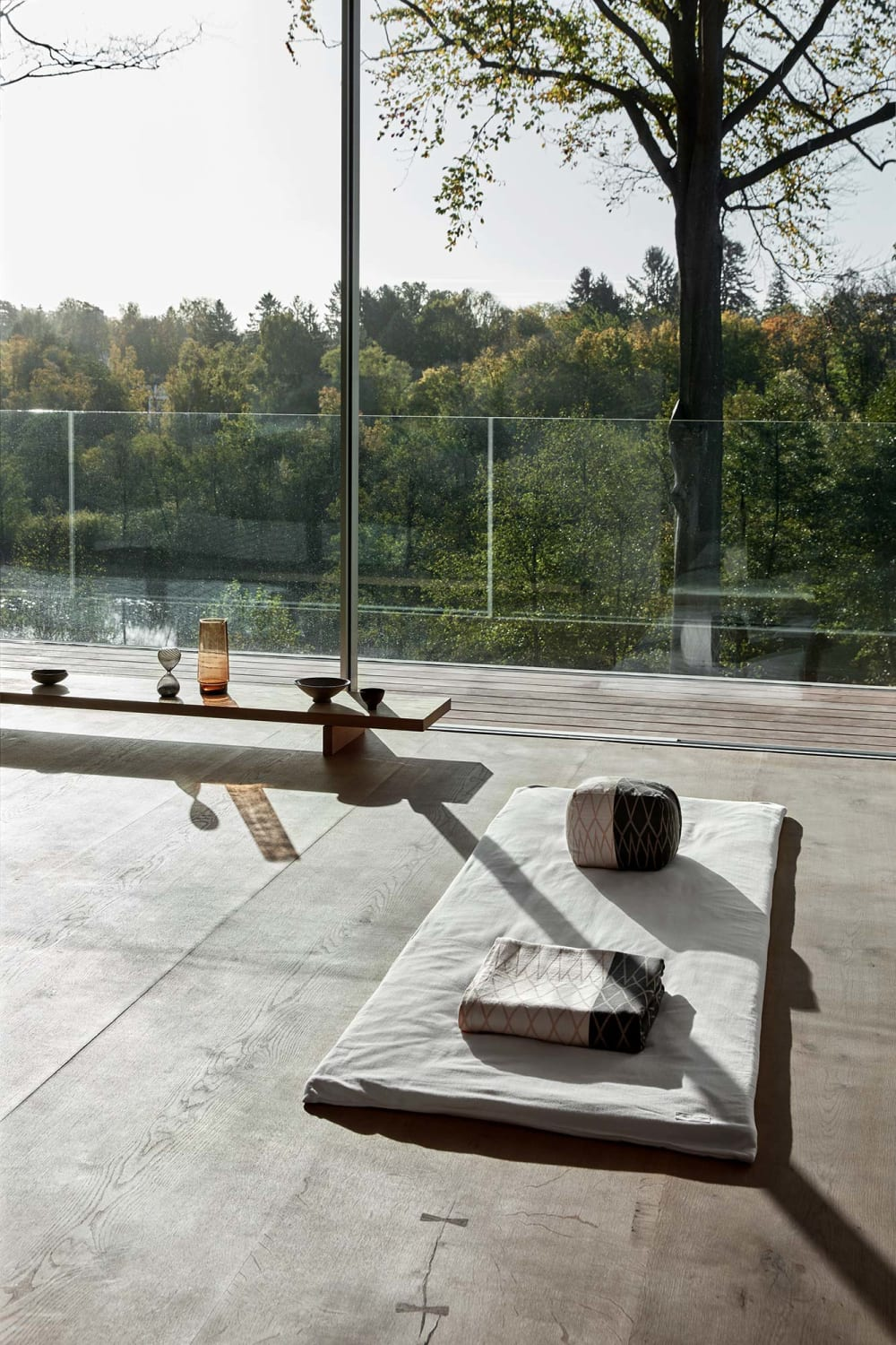 """Meditation space on a room with a fully glazed wall and a view onto nature.<span class=""""sr-only""""> (opened in a new window/tab)</span>"""