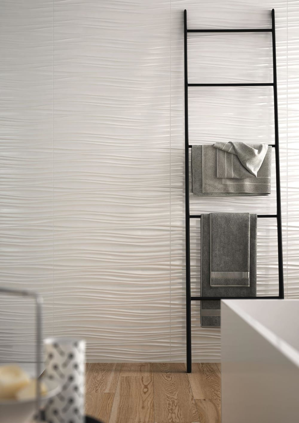 "Bathroom wall with textured tiles recalling the wavy shape of sand moved by the wind.<span class=""sr-only""> (opened in a new window/tab)</span>"